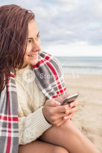 Woman covered in blanket with cellphone at beach