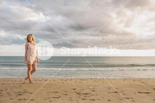 Woman in summer dress walking on beach