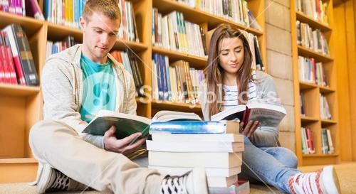 Students reading books on the library floor