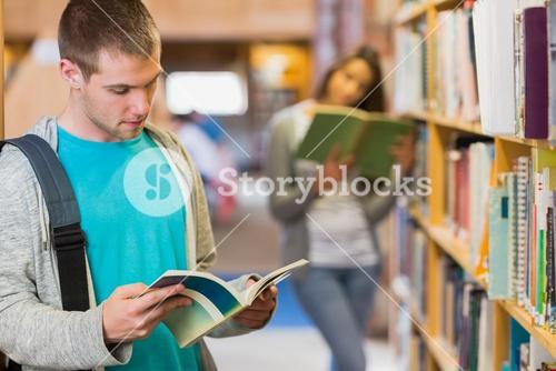 Students reading by bookshelf in the library