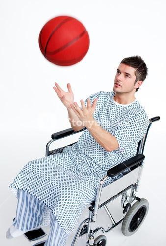 Patient in wheelchair playing with a basket ball