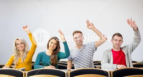 College students raising hands in the classroom