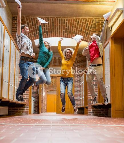 Group of students jumping in college corridor
