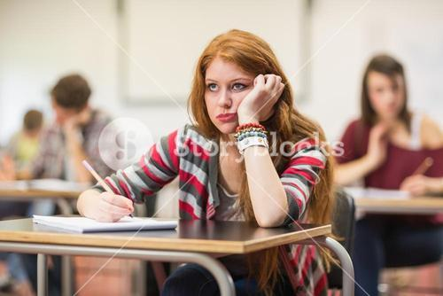 Bored female student with others writing notes in classroom