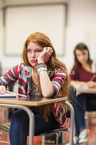 Bored female student sitting in classroom
