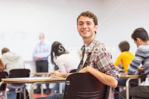 Male with blurred teachers students in classroom