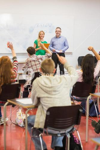 Students raising hands in the classroom