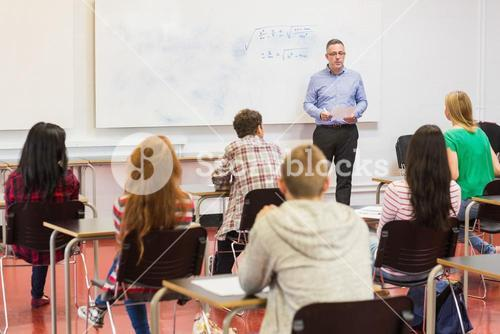 Attentive students with teacher in the classroom