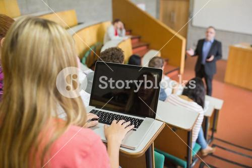 Female using laptop with students and teacher at lecture hall