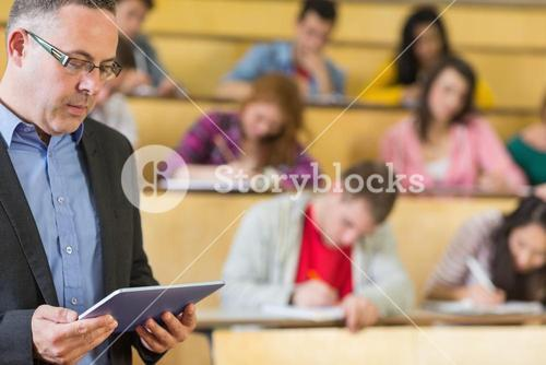 Teacher using tablet PC with students at lecture hall