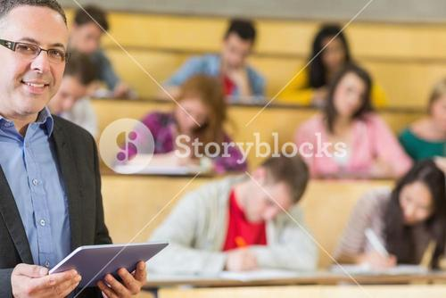 Teacher using tablet PC with students sitting at lecture hall