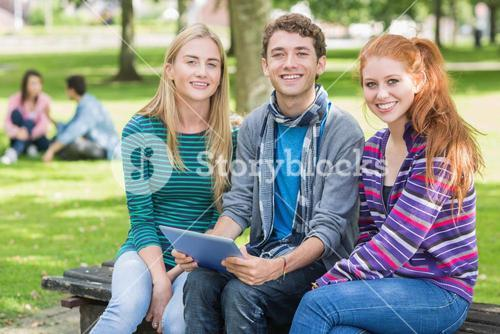 College students with tablet PC in park