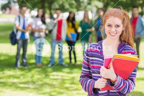 College girl holding books with students in park