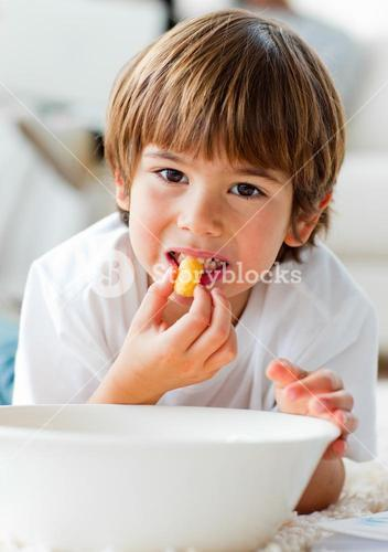 Cute little boy eating chips lying on the floor