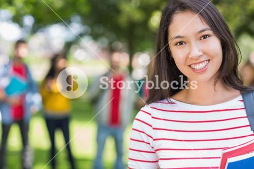 Close up of college girl with blurred students in park