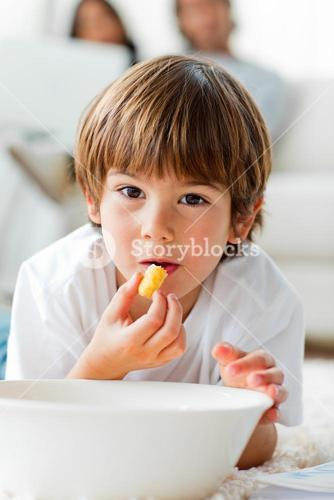 Beautiful little boy eating chips lying on the floor