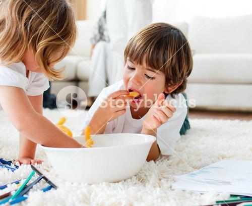 Cute children eating chips and drawing