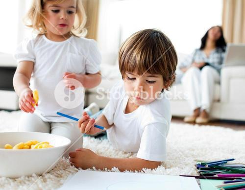 Adorable children eating chips and drawing