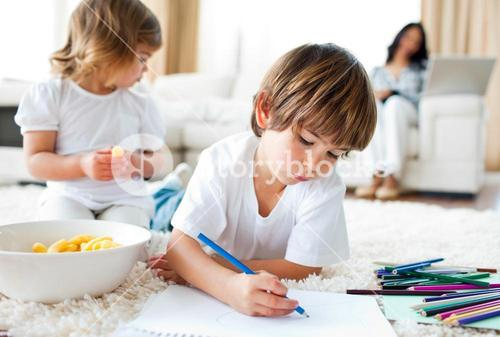 Happy children eating chips and drawing