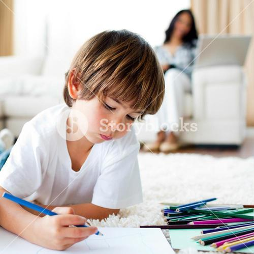Concentrated little boy drawing and his sister eating chips