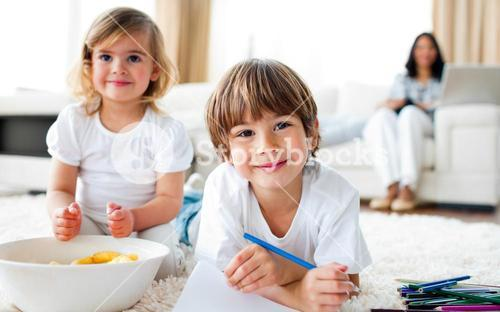 Smiling siblings eating chips and drawing