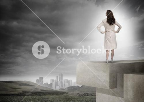 Businesswoman in front of cloudy sky and landscape with buildings