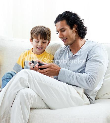 Caring father and his son sitting on a sofa