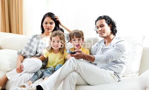 Excited little boy watching TV with his family