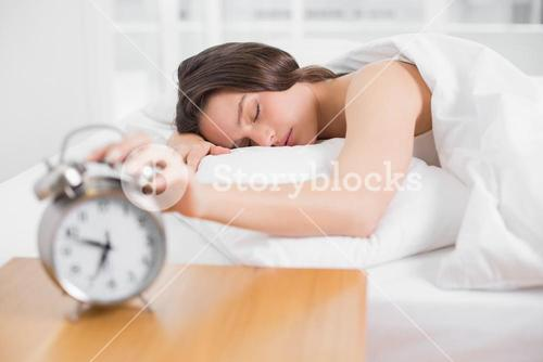 Woman in bed with eyes closed extending hand to alarm clock