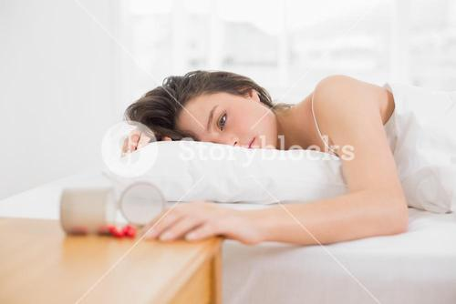 Woman lying in bed by spilt bottle of pills on table