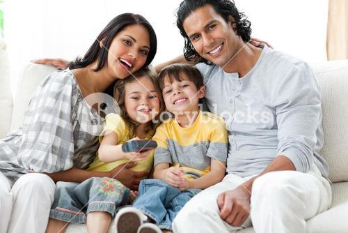 Happy family watching TV together sitting