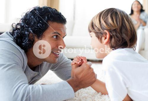 Cute little boy and his father armwrestling