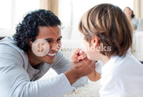 Cheerful father and his son armwrestling