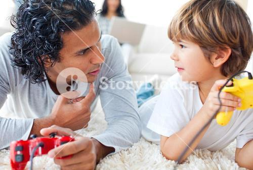 Father and his little boy playing video games lying on the floor