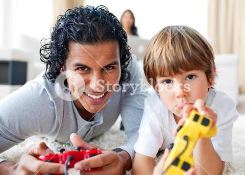 Happy father and his son playing video games lying on the floor
