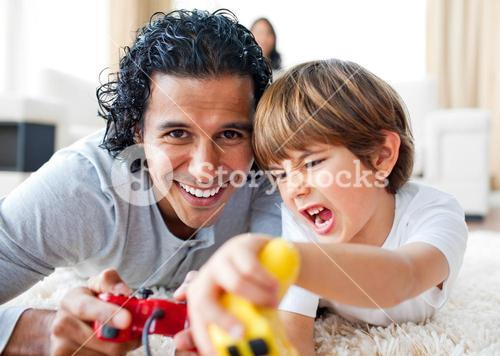 Excited little boy and his father playing video games lying on the floor