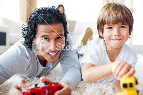Cheerful father and his son playing video games lying on the floor