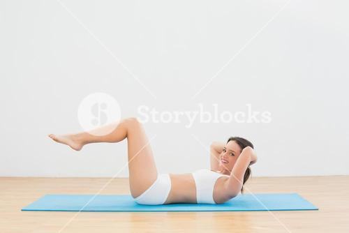 Sporty woman doing sits up at fitness studio