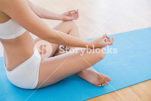 Side view of a slim cropped woman in lotus pose