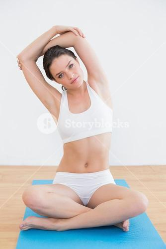 Toned woman stretching in fitness studio