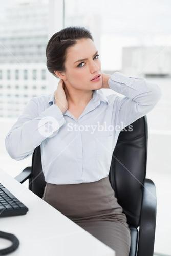 Businesswoman with neck pain sitting at office