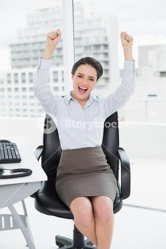 Elegant and happy businesswoman clenching fists in office