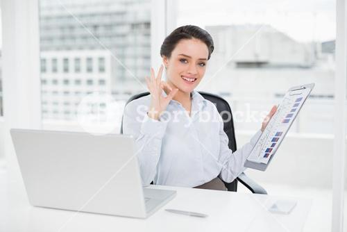 Businesswoman with graphs and laptop gesturing okay sign in office