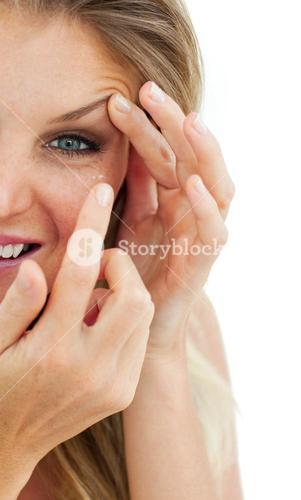 Charming woman putting a contact lens