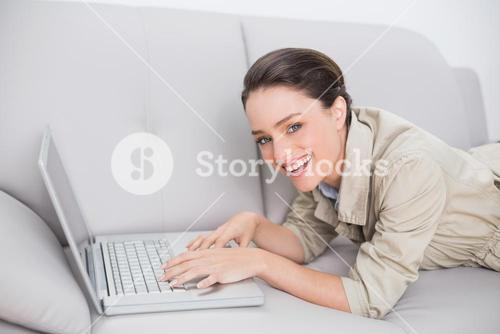 Beautiful woman using laptop on sofa at home