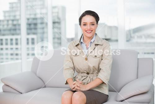 Smiling well dressed woman sitting on sofa at home