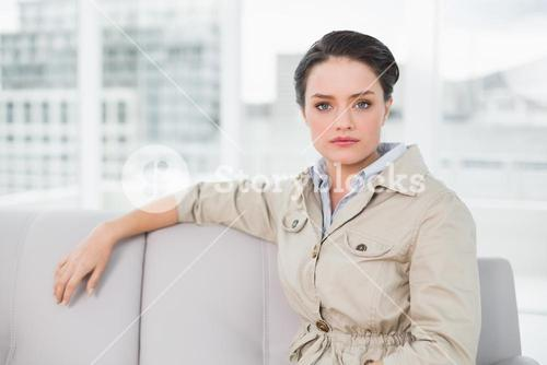 Serious well dressed woman sitting on sofa at home