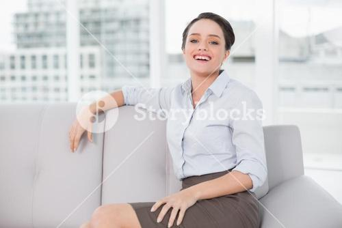 Smiling well dressed young woman sitting on sofa