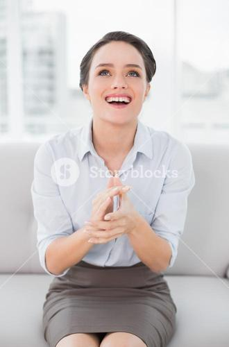 Smiling well dressed woman applauding while looking up