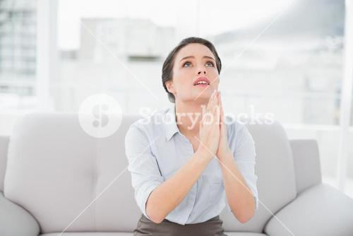 Worried well dressed woman with joined hands looking up